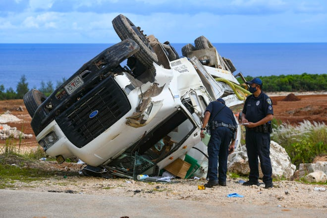 Officers with the Guam Police Department Highway Patrol Division conduct an investigation of the crash of a Detry Plumbing waste water tanker truck, along the access road to the Marbo Caves in Pagat, Mangilao on Thursday, Oct. 1, 2020. There were two occupants in the vehicle when the truck overturned and crashed. One person was transported to the hospital but the other person died in the crash.