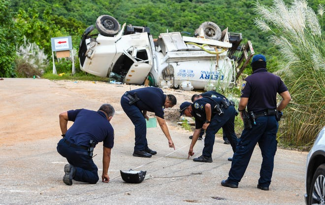 Officers with the Guam Police Department Highway Patrol Division conduct an investigation of the crash of a Detry Plumbing waste water tanker truck along the access road to the Marbo Caves in Pagat, Mangilao, in this Oct. 1 file photo.