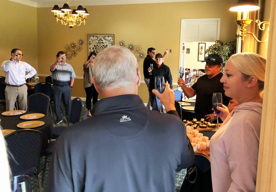 Celebrating his purchase of Henderson Country Club last Tuesday, Charles Morris (second from right) toasts with club members, directors, staff and others in the banquet room of the clubhouse. (Photo by Chuck Stinnett)