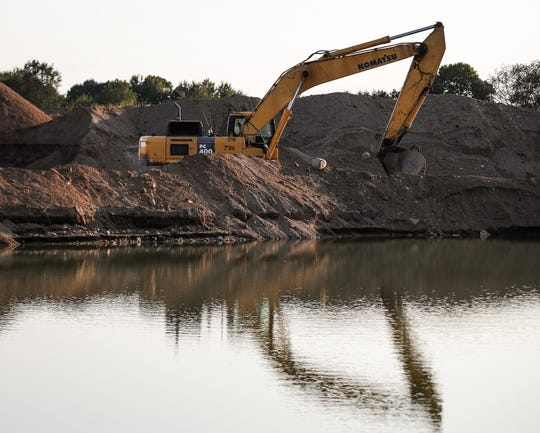 A giant excavator sits on the edge of a small pond at Beaver Materials gravel pit in Strawtown, Ind., Thursday, September 24, 2020.