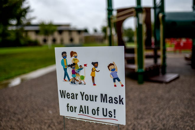 A sign posted near playground equipment reminds people to wear masks behind Pinecrest Elementary School photographed on Wednesday, Sept. 30, 2020, in East Lansing.