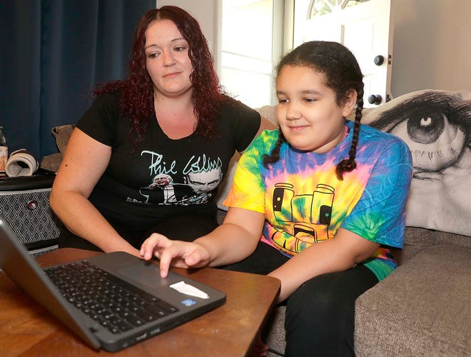 Jacquelyn Melka watches her daughter, Payton Robinson, working on homework. They are doing virtual school during the pandemic.