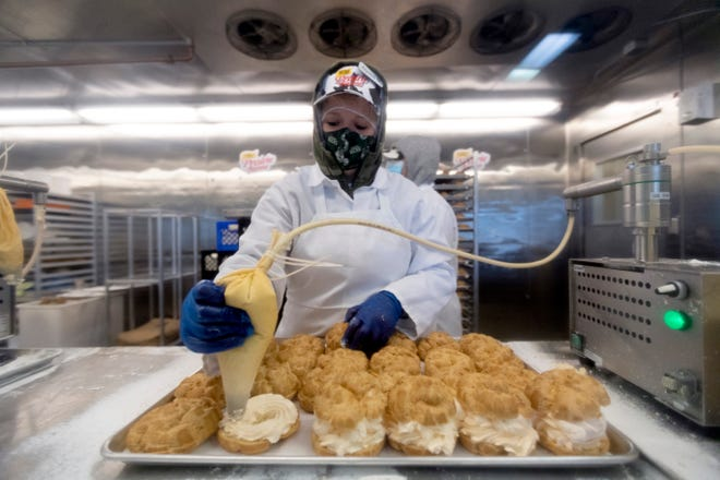 A worker fills cream puffs on the first day of sales for pumpkin spice cream puffs Thursday, October 1, 2020 at State Fair Park in West Allis, Wis. The limited time cream puffs are being sold in 3-packs for $12 and 6-packs for $22. Only the new pumpkin spice flavor is being sold on these days; Original Cream Puffs will not be available. The puffs are available through Sunday.