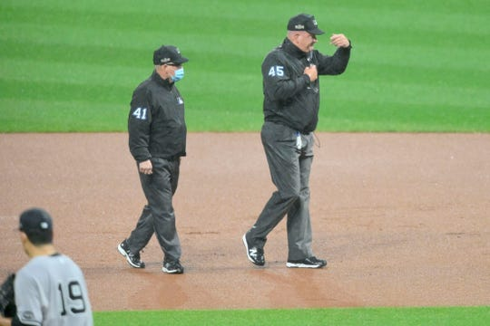 Sep 30, 2020; Cleveland, Ohio, USA; Second base umpire Jerry Meals (41) watches as first base umpire Jeff Nelson (45) waves the players off the field during a rain delay in the first inning at Progressive Field.