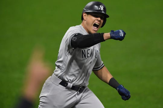 New York Yankees' Gio Urshela celebrates while running the bases after hitting a grand slam off Cleveland Indians relief pitcher James Karinchak in the fourth inning of Game 2 of an American League wild-card baseball series Wednesday, Sept. 30, 2020, in Cleveland.