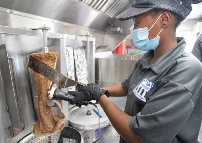 Amelia Cummings shaves meat off a gyro spit at Greek's Catering & Events food truck along Summit Boulevard in Pensacola on Thursday, Oct. 1, 2020.