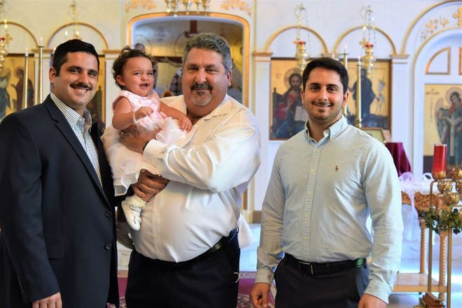 From left, Stelios Peterson, Dean Peterson -- holding Alexia Peterson -- and Pantelis Peterson pose for a photo at Alexia's baptism.