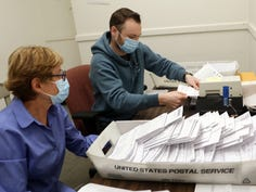 From left, Meris Sparrow watches as Patrick Seiler time stamps a ballot  at the Dutchess County Board of Elections in Poughkeepsie Oct. 1, 2020.