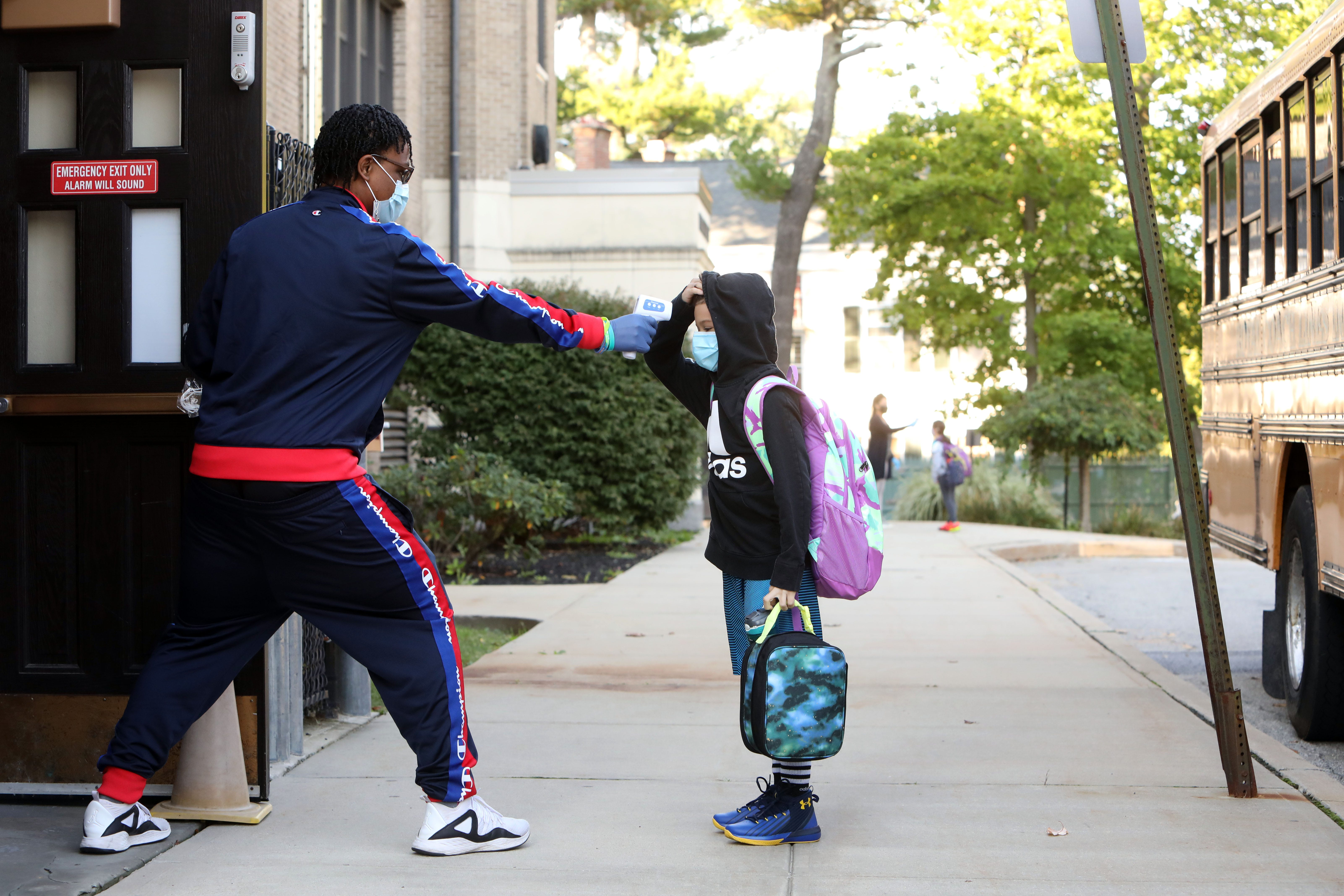 Determined to provide in-person instruction while preventing the spread of COVID-19 schools implemented safety measures including morning health screenings. As seen here in October, teaching assistant Jalay Knowles takes the temperature of a fifth-grader while students arrive at Ossining's Roosevelt Elementary School.
