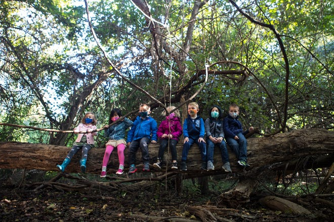 Prekindergarten students at St. Anne's Episcopal School sit on a log together as they have class Monday, Sept. 21, 2020, in Middletown.