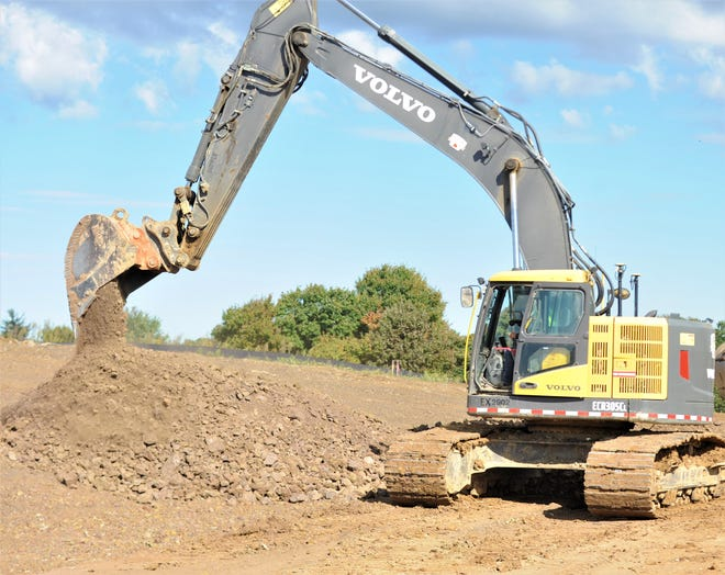 A Shelly and Sands employee uses a backhoe to move dirt for the water and sewer infrastructure being installed at the National Road Business Park on Thursday. The project also includes the building of the main entrance and should be finished by Nov. 30.