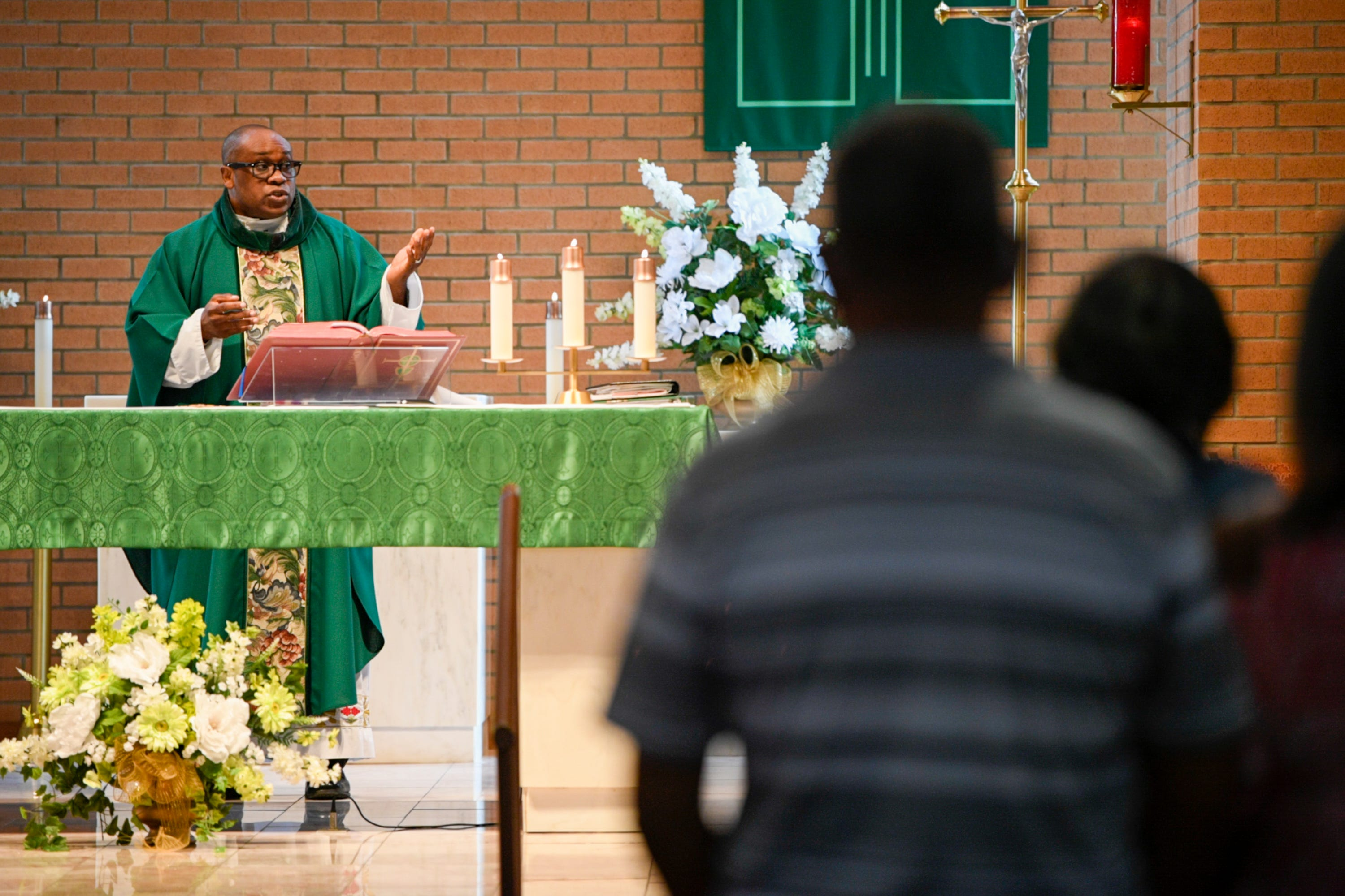 Parishioners stand in Our Lady of Grace Catholic Church in Reserve, La., during a sermon by the Rev. Fr. Christopher Chike Amadi.