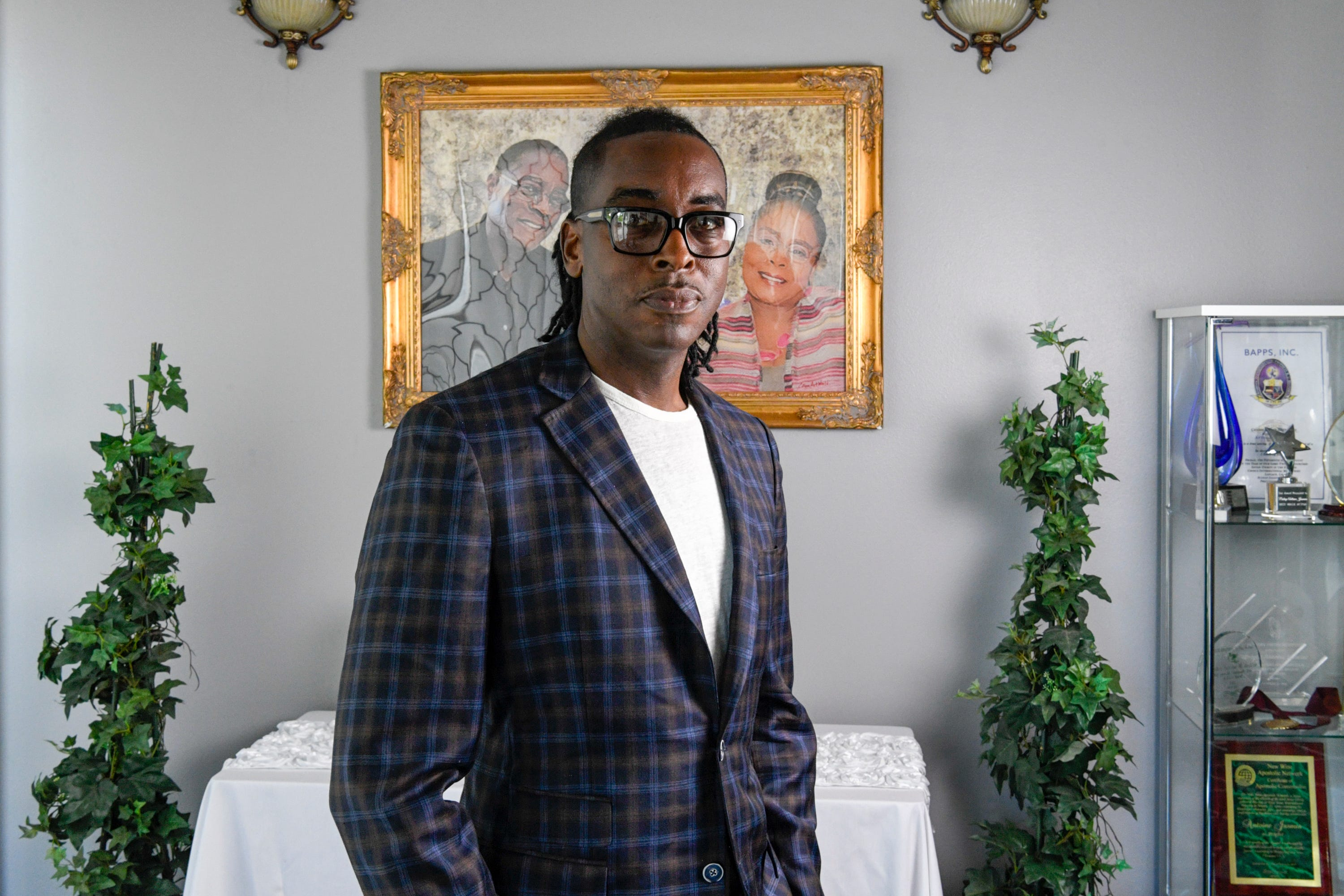 The Rev. Antoine Jasmine of Choice International Ministries poses for a portrait in front of a photo of his parents, who both lived in Reserve, La., and died four hours apart from COVID-19 complications in April.