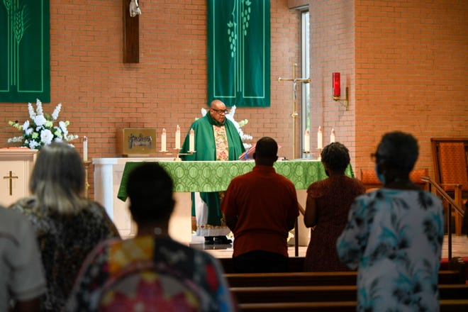 Parishioners stand in Our Lady of Grace Catholic Church in Reserve, LA., during a sermon by the Rev. Fr. Christopher Chike Amadi. Black Americans have faced increased incidents of COVID-19-related illness and death during the pandemic.