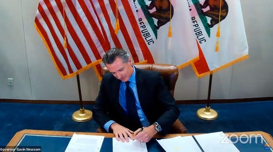 This image made from video from the Office of the Governor shows California Gov. Gavin Newsom signing into law a bill that establishes a task force to come up with recommendations on how to give reparations to Black Americans on Sept. 30, 2020.