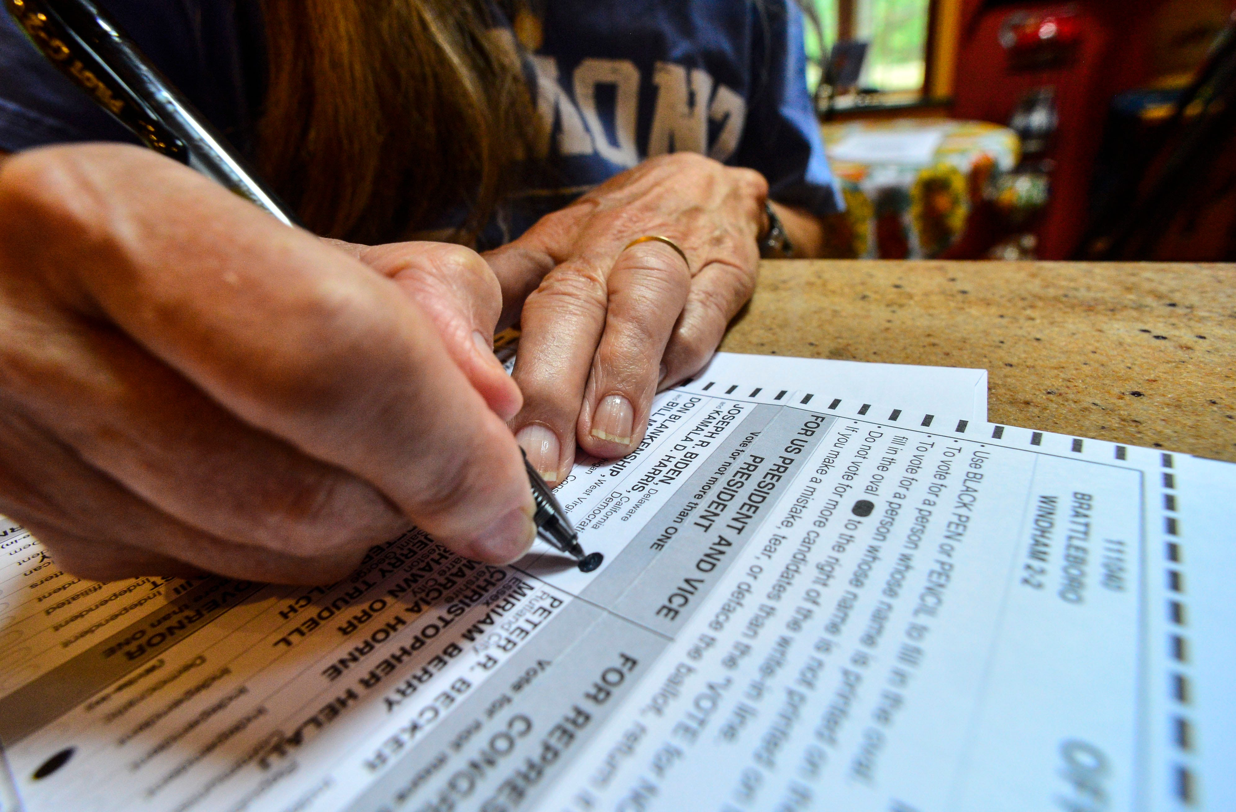 Susan Avery, of Brattleboro, Vt., casts her vote for Democrat presidential candidate, Joe Biden, while filling out her November election ballot that she received in the mail on Monday, Sept. 28, 2020.