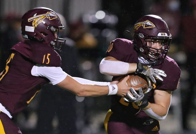 Walsh quarterback Matt Natale, left, hands the ball off to running back Will Rumple during the first half of a football game at Walsh Jesuit High School, Thursday, Oct. 1, 2020, in Cuyahoga Falls, Ohio. [Jeff Lange/Beacon Journal]