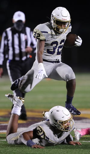 Hoban running back Lamar Sperling, top, hurdles teammate Victor Dawson as he rushes to a first down during the second half of a football game at Walsh Jesuit High School, Thursday, Oct. 1, 2020, in Cuyahoga Falls, Ohio. [Jeff Lange/Beacon Journal]