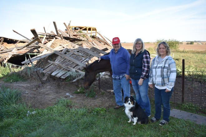Rick Reed, his girlfriend Laura Perisho, his sister Roxanne Reed Mehlisch and dog Cali pose with Mac, the horse, next to the ruins of a historic barn on Reed's farm near Zearing.