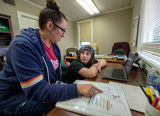 Jane O'Neill, of Falls, helps her fifth-grader James learn from a remote setting at the family's business in Middletown.