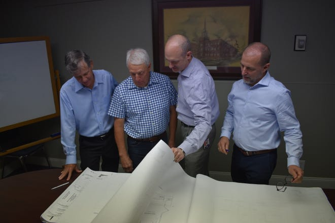 Poring over the architectural drawings one more time are John Lanning, chairman of the capital development committee; Greg Dalton, chairman of the building and grounds committee; Dale Johnson, chairman of the deacons; and Pastor James Biesiadecki who spearheaded the project's committees.