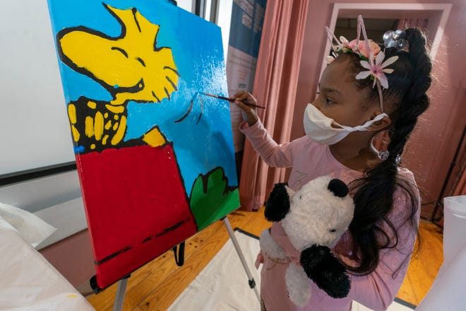 """Kaley Williams, 8, paints a panel of a """"Peanuts"""" mural that will be placed in the outpatient pediatric floor of One Brooklyn Health at Brookdale Hospital in New York. It's part of a celebration marking the comic's 70th anniversary."""