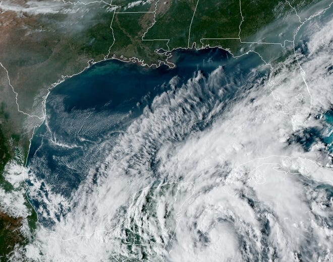 A satellite image shows a tropical depression swirling Friday afternoon in the Caribbean Sea off Mexico's southern Yucatan Peninsula. It's expected to become Tropical Storm Gamma this weekend.