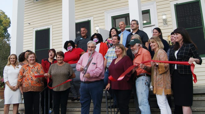 MacDonell United Methodist Children's Services Executive Director Kevin Champagne cuts a ribbon Thursday officially opening the group's new home for extended foster care.