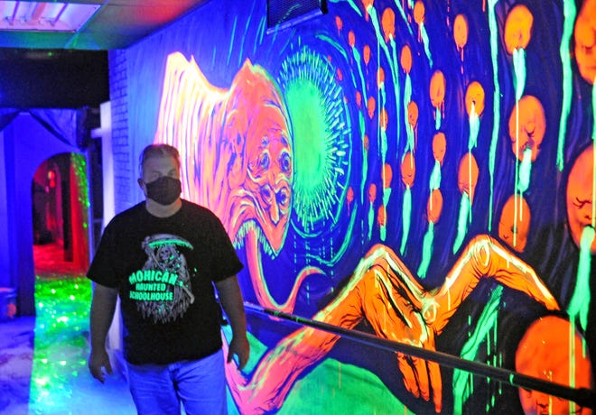 John Gepperth, co-owner of the Mohican Haunted Schoolhouse, stands in front of a hand-painted mural in the haunt. Gepperth and his team have worked to update the haunt to comply with social distancing guidelines.
