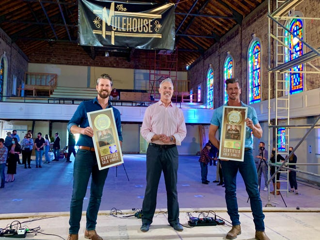 "The Mulehouse founder and renowned radio DJ Blair Garner, center, presents Columbia country duo High Valley with gold records awarded for their single, ""She's With Me."" (Staff photo by Jay Powell)"
