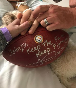 The parents of McDowell's Johnny Heubel hold Johnny's hand on the gift of a signed football sent by Pittsburgh Steelers running back James Conner, a McDowell graduate. Heubel is recovering from two brain surgeries in a Pittsburgh hospital.