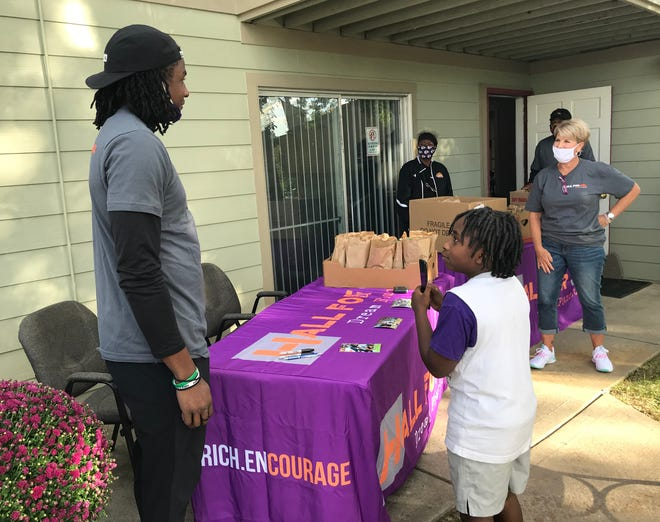 Deiondre Hall, a Blue Springs High School graduate who went on to play in the NFL, spent Wednesday afternoon filling lunch sacks that he and his Hall for One Dream Foundation team passed out to youngsters Thursday at Autumn Place Apartments in Blue Springs. Joining Hall, left, was Community Services League Blue Springs site coordinator Melodie Chrisman, right.