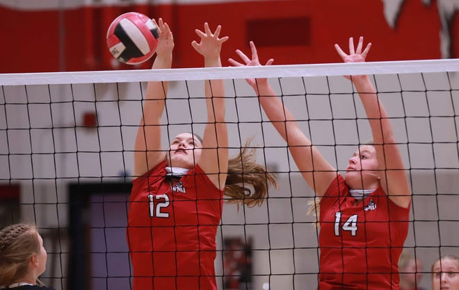 Winfield-Mt. Union's Bradie Buffington (12) and Madie Anderson (14) jump at the net for the block in their win over Hillcrest Academy on Thursday at Winfield.