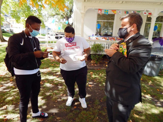 Pouwei Tombri of Nigeria and Schael Michanol of France sample a treat from Vietnam handed out by Iowa Weselyan Univeisty provost DeWayne Frazier Wednesday outside the renovated home of the Center for International Education at the university in Mount Pleasant. Tombri and Michanol are two of the 87 international IWU students who can use the renovated two-story house as a cultural centerpoint.