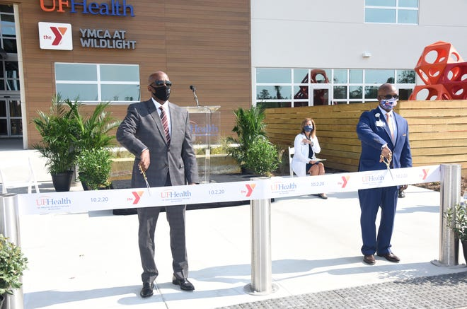 Leon Haley Jr., CEO of UF Health Jacksonville (right) and Eric Mann, president/CEO, First Coast YMCA, cut a ribbon to open their agencies' combination rehabilitation and fitness center in the Wildlight community near Yulee. Behind them is Jeanne Bradshaw, director of rehabilitative services for UF Health Jacksonville.