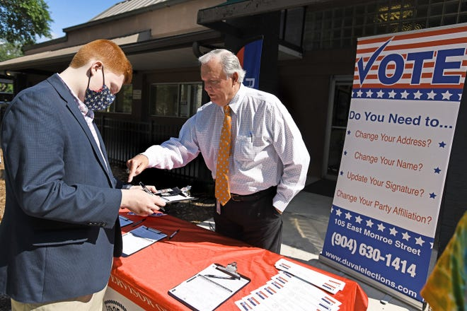 Supervisor of Elections Mike Hogan in June helps Jack Rowan as he fills out his voter registration information during a press conference at the Supervisor of Elections office.
