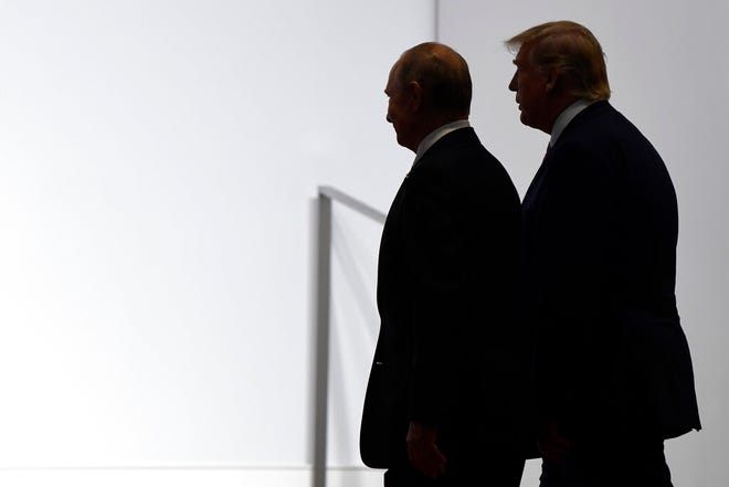 In this June 28, 2019, file photo, President Donald Trump and Russian President Vladimir Putin walk to participate in a group photo at the G20 summit in Osaka, Japan.  Most Americans are concerned at least somewhat by the potential for foreign interference in November's election, and a majority believes that Russian sought in 2016 to influence the outcome of that race.