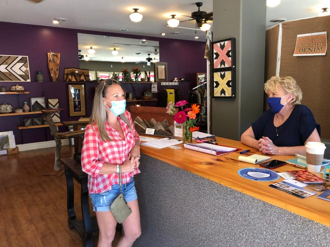 Jo Anne Alliet at the counter of a pop up shop in Naples last Saturday, talks with customer Sally Woods of Pittsford.