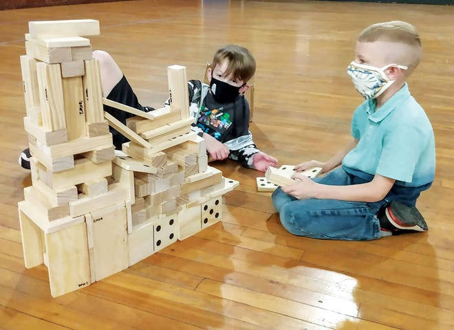 Children in the program build a structure with blocks.
