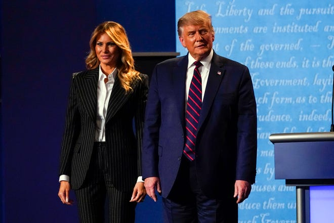 President Donald Trump stands on stage with first lady Melania Trump Wednesday following the presidential debate. Trump announced early Friday he had been diagnosed with the coronavirus.