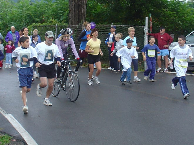 In this file photo from around 2004, Nick Angelicola, far left, a Utica resident and Rome native, runs next to family friend Jerry Spaziani during the Alzheimer's Association Walk to End Alzheimer's. Angelicola, now 28, was only 10 was his maternal grandmother, whose photo is on his t-shirt, was diagnosed with early-onset Alzheimer's disease.