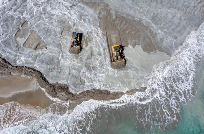 Bulldozers from Weeks Marine spread sand on Midtown Beach in March. [GREG LOVETT/PALMBEACHDAILYNEWS.COM]