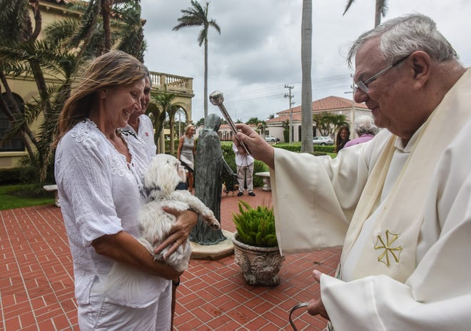 Maryanne Horwath, of Palm Beach, holds Mickey, a Maltese, as Monsignor Thomas J. Klinzing blesses him at St. Edward in October 2017.