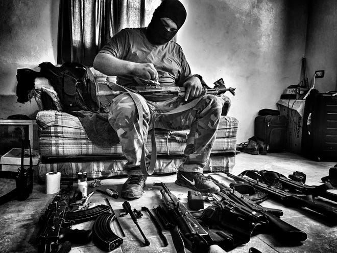 "A soldier from the Sinaloa drug cartel cleans guns in the National Geographic documentary on migration ""Blood on the Wall,"" which premieres Sept. 30, 2020. (Nick Quested/National Geographic/TNS)"
