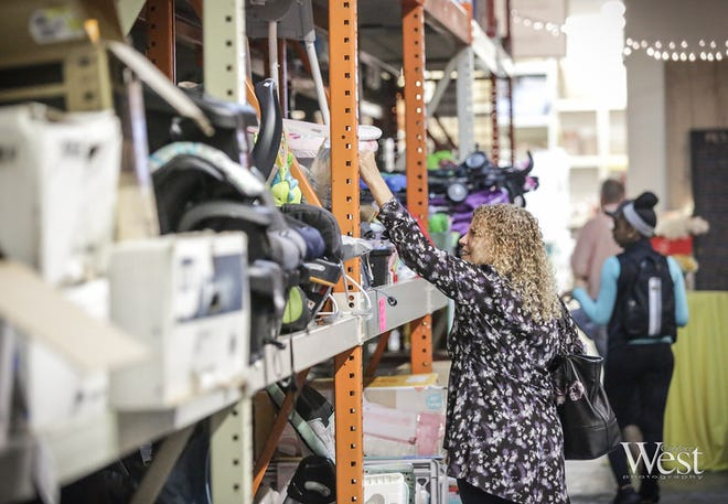 Attendees to an open house at the Morningday Community Solutions' warehouse in March 2019 check out the organization's offerings, which are discounted 70%-80% off of retail to qualified non-profits. [Photo by CandaceWest.com]