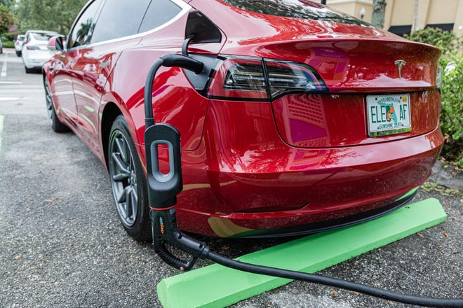 Using a Tesla charging adapter, a Tesla sedan gets a charge at the new EVolution charging station at Midtown in Palm Beach Gardens, Friday, October 2, 2020.