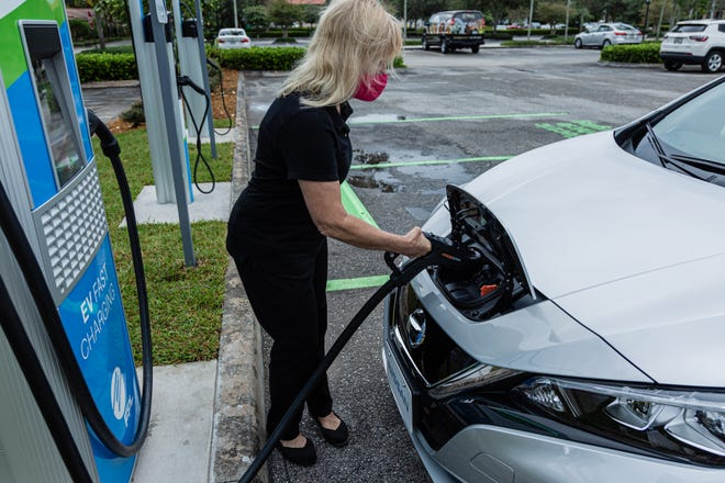 Beth Bowers, Project Manager of FPL EVolution connects the charging coupling to the Nissan Leaf electric car at the new EVolution charging station at Midtown in Palm Beach Gardens, Friday, October 2, 2020. There are four Level 3 (fast) charging stations, and two Level 2 (slower charging) stations at the site. Florida Power & Light is commemorating National Drive Electric Week with the debut of a new electric vehicle universal fast-charging station at Mainstream in Midtown in Palm Beach Gardens. Customers will be charged about 30 cents per kilowatt hour to charge their electric vehicles. [JOSEPH FORZANO/palmbeachpost.com]