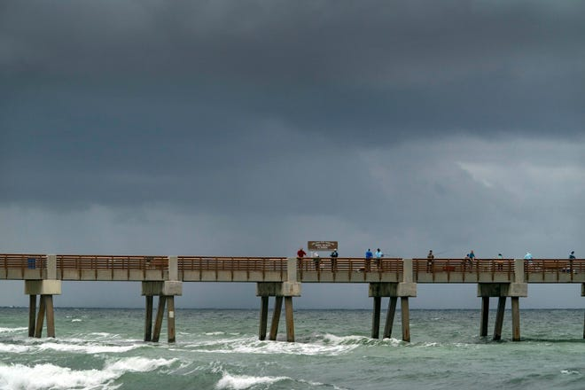 Fishermen cast their lines Friday at the Juno Beach Pier as showers roll in from the north.