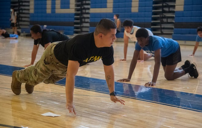 Army Sgt. Jesus Ruiz demonstrates a pushup during high intensity interval training for Mountain House High School football players in the school's gym in Tracy.