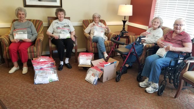 Pictured, five Vista Veranda residents pose with art kits they helped assemble. The kits were then donated to Ravenna High School's art department.